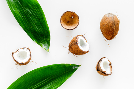 Photo pour Tropical composition with coconut. Whole coconuts and coconut cut in half near palm leaves on white background top view. - image libre de droit