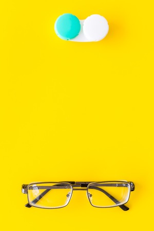 Foto de Way to improve vision. Contact lenses in container near glasses on yellow background top view. - Imagen libre de derechos