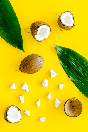 Photo pour Coconut background. Whole and cut coconuts, pulp and palm leaves on yellow background top view. - image libre de droit