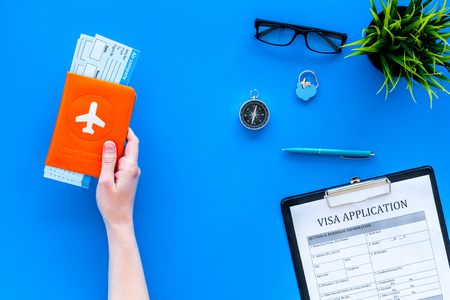 Photo pour Planning vacation. Visa processing. Hand hold airplane tickets in passport cover with airplane silhouette near visa application form, compas on blue background top view. - image libre de droit