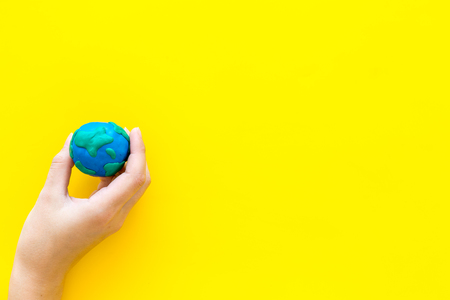 Photo pour Earth. Hand hold plastiline symbol of planet Earth globe on yellow background top view space for text - image libre de droit