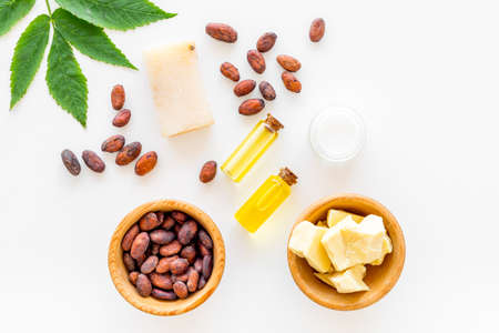 Foto de Natural organic cosmetics based on cocoa butter. Cocoa beans and cocoa butter, soap, cream, oil or lotion in small bottles on white background top view. - Imagen libre de derechos