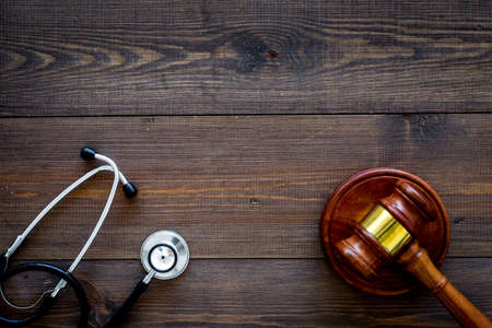 Photo pour Medical law, health law concept. Gavel and stethoscope on dark wooden background top view copy space - image libre de droit