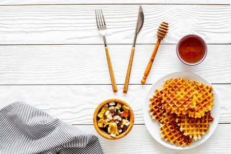 Photo for Traditional belgian waffles near dried fruit, nuts and honey on served table with tablecloth on white wooden background top view copy space - Royalty Free Image