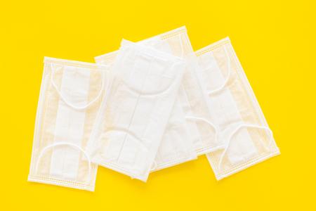 Photo pour Flu prevention. Medical face masks on yellow background top view copy space - image libre de droit