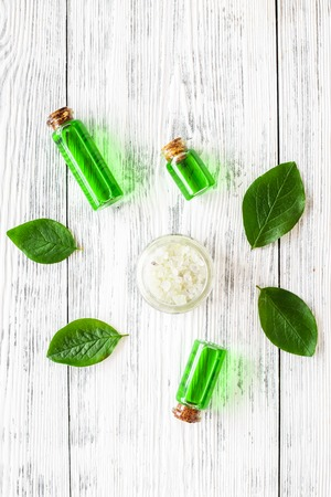 Photo pour Natural hipoallergenic cosmetics with tea tree essential oil. Oil, lotion, leaves on white wooden background top view. - image libre de droit