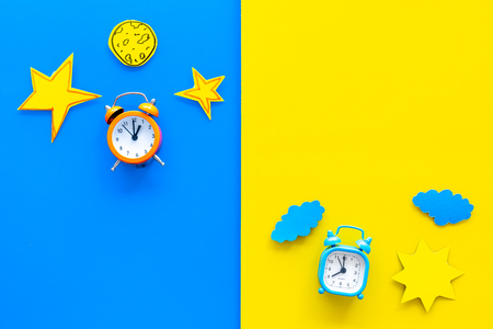 Photo pour Sleep time, clock on the bed and time to awake concept. Alarm clock near sun, moon, stars cutout on blue and yellow background top view. - image libre de droit