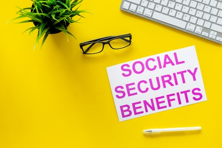 Photo pour Printed words social security benefits on yellow office desk background with computer keyboard top view copy space - image libre de droit