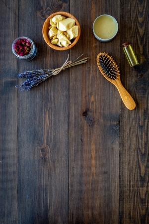 Foto de Natural oil for hair. Jojoba, argan, coconut oil near bunch of lavender and hairbrush on dark wooden background top view copy space - Imagen libre de derechos