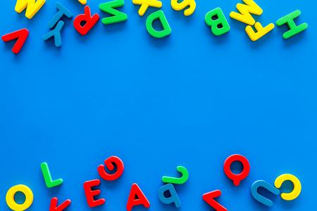 Foto de Alphabet for kids concept. English letters in disorder on blue background top view. - Imagen libre de derechos