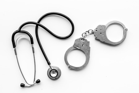 Foto de Medical lawsuit. Arrest for medical crime concept. Handcuff near stethoscope on white background top view. - Imagen libre de derechos