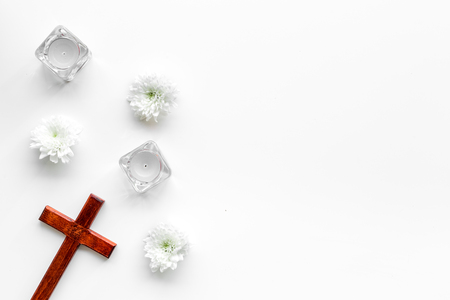 Photo pour Funeral concept. Wooden cross near candles and flowers on white background top view copy space - image libre de droit
