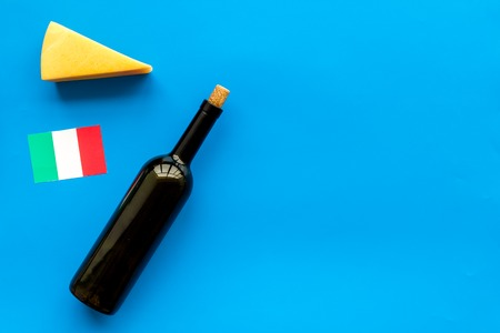 Photo for Gastronomical tourism. Italian food symbols. Italian flag, cheese parmesan and bottle of red wine on blue background top view copy space - Royalty Free Image