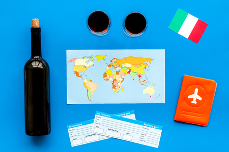 Photo for Gastronomical tourism. Italian food symbols. Passport and tickets near italian flag, bottle of red wine, map of the world, cheese parmesan on blue background top view - Royalty Free Image