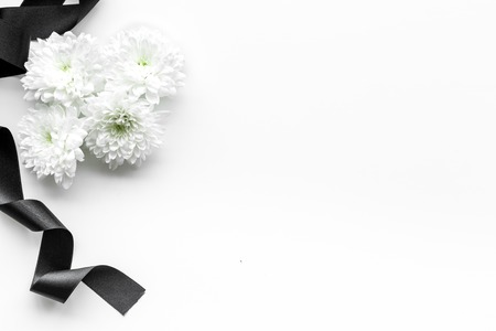 Photo pour Funeral symbols. White flower near black ribbon on white background top view space for text - image libre de droit