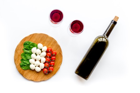 Photo for Italian cuisine, food concept. Italian flag made of mozzarella, tomatoes, basil on wooden cutting board near glass of red wine and wine bottle on white background top view - Royalty Free Image
