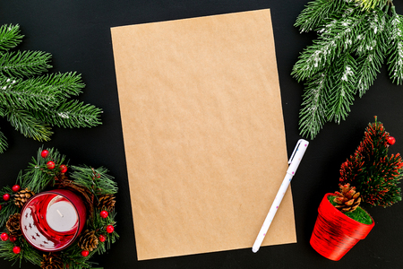 Foto per New Year or Christmas mockup. Template for letter to Santa, list of plans and goals for New Year, wishlist near fir branches, candle, festive tree on black background top view - Immagine Royalty Free