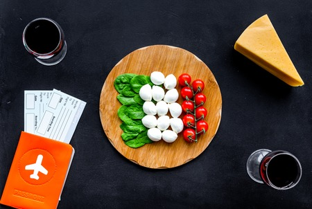 Photo for Passport and tickets near italian food like cheese, tomato, wine on black background - Royalty Free Image