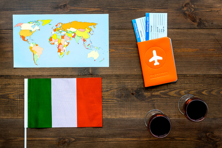 Photo for Passport and tickets near italian flag, glass of red wine, map of the world on dark wooden background - Royalty Free Image