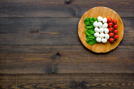 Photo for Italian flag made of mozzarella cheese, cherry tomatoes, green basil on wooden cutting board on wooden background - Royalty Free Image