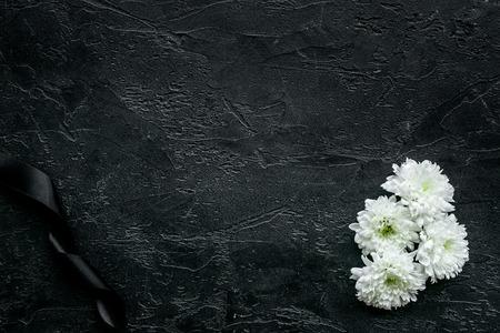 Foto de White flower near black ribbon on black background top view. - Imagen libre de derechos
