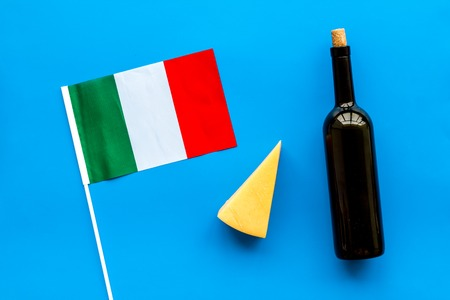 Photo for Italian flag, cheese parmesan and bottle of red wine on blue background top view. - Royalty Free Image