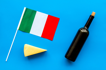 Photo for Gastronomical tourism. Italian food symbols. Italian flag, cheese parmesan and bottle of red wine on blue background top view - Royalty Free Image