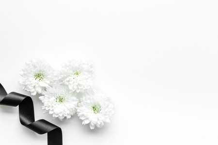 Foto de Funeral symbols. White flower near black ribbon on white background top view copy space - Imagen libre de derechos