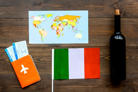 Photo for Gastronomical tourism. Italian food symbols. Passport and tickets near italian flag, bottle of red wine, map of the world on dark wooden background top view. - Royalty Free Image