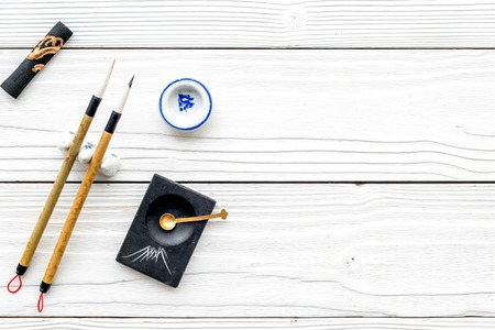 Foto de Accessories for Chinese or Japanese calligraphy. Special writing pen, ink on white wooden background top view copy space - Imagen libre de derechos