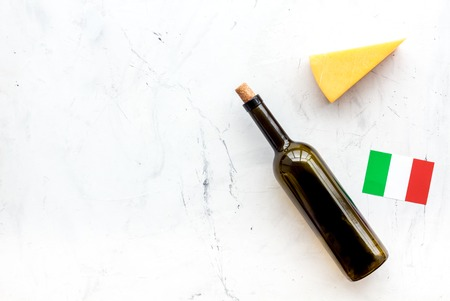 Photo for Gastronomical tourism. Italian food symbols. Italian flag, cheese parmesan and bottle of red wine on white background top view. - Royalty Free Image