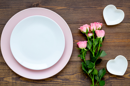 Foto de Simple color table setting for celebration with roses, pink plates and heart-shaped saucers on wooden kitchen table background top view mock up. - Imagen libre de derechos