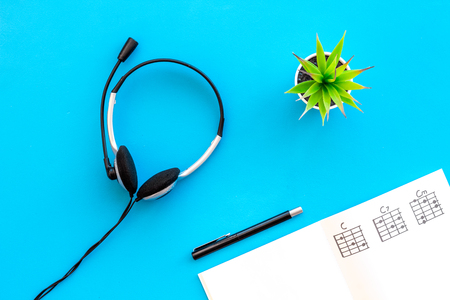 Photo for Songwriter or dj work place with notes and headphones on desk blue background top view - Royalty Free Image