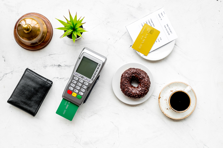 Foto de Electronic payments. Pay the bill by card concept. Bank card inserted in payment terminal near bill, service bell, coffee, donut on white stone background top view - Imagen libre de derechos