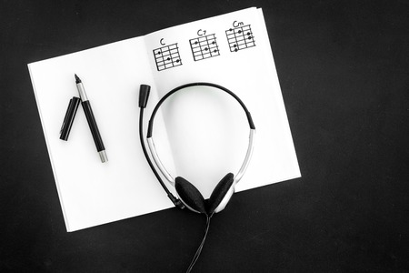 Photo for Desk of musician for songwriter work with headphones and notes black background top view - Royalty Free Image