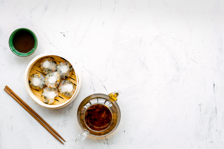 Foto de Dinner in Chinese restaurant with dim sum, sticks and herbal tea on marble background top view space for text - Imagen libre de derechos