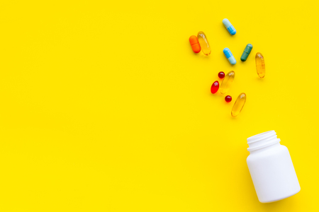 Foto de Close up of an open bottle of medicine and its lid. Several pills are lying on yellow desk. Pharmacology and medical supplies. Top view mock-up - Imagen libre de derechos