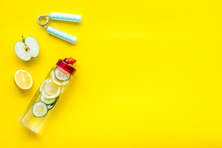 Photo pour Healthy fruit water for sport, fitness. Bottle of water with lemon and cucumber near sport equipment on yellow background top view copy space - image libre de droit