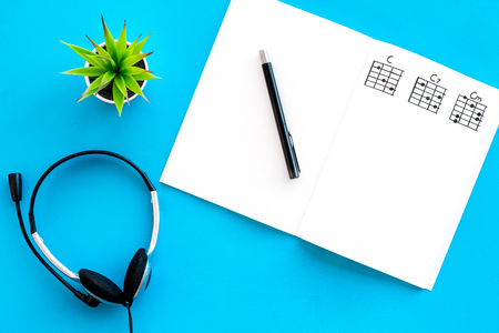 Photo for songwriter or dj work place with notes and headphones on blue background top view mock up - Royalty Free Image