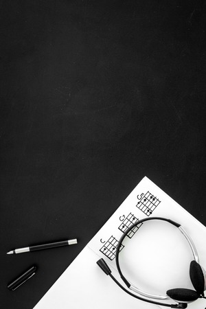 Photo for Desk of musician for songwriter work with headphones and notes black background top view mockup - Royalty Free Image