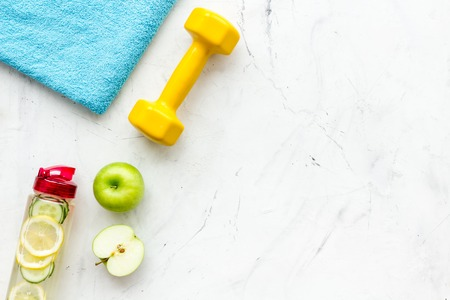 Photo pour Healthy fruit water for sport, fitness. Bottle of water with lemon and cucumber near sport equipment dumbbells on white stone background top view copy space - image libre de droit