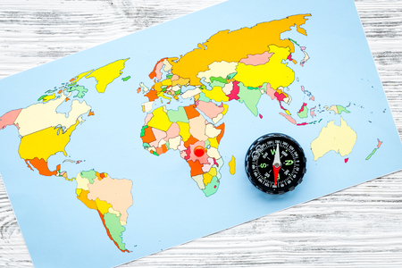 Photo pour Travel direction and trip planning concept with compass and map of the world on gray wooden background top view - image libre de droit