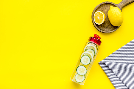 Photo pour Make detox fruit water. Slices of lemon and cucumber in bottle on yellow background top view space for text - image libre de droit