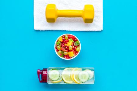 Photo pour Healthy lifestyle, healthy habits. Detox water, fruit salad, sport equipment dumbbells on blue background top view - image libre de droit