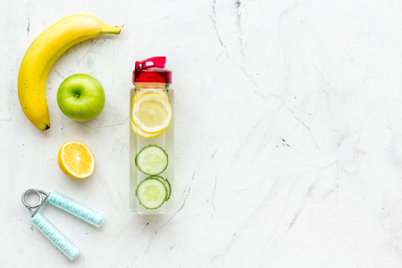 Photo pour Healthy fruit water for sport, fitness. Bottle of water with lemon and cucumber near sport equipment on white stone background top view space for text - image libre de droit