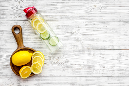 Photo pour Detox infused water with slices of lemon and cucumber in bottle on white wooden background top view. - image libre de droit