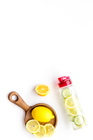 Photo pour Detox infused water with slices of lemon and cucumber in bottle on white background top view copy space - image libre de droit