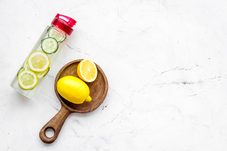 Photo pour Detox infused water with slices of lemon and cucumber in bottle on white stone background top view. - image libre de droit
