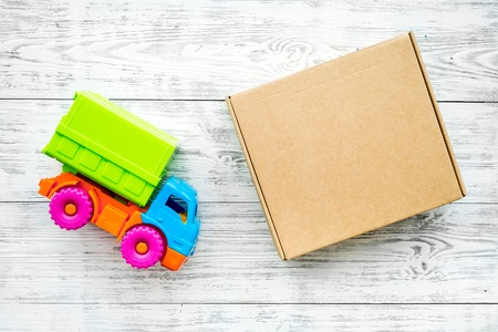 Photo pour Cargo delivery concept. Cardboard box near toy truck on white wooden background top view. - image libre de droit
