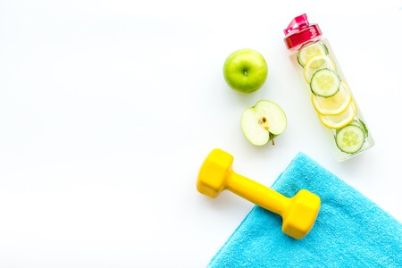 Photo pour Healthy fruit water for sport, fitness. Bottle of water with lemon and cucumber near sport equipment dumbbells on white background top view copy space - image libre de droit